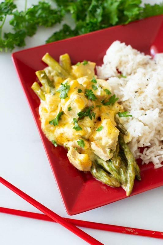 Red plate containing asparagus, with chicken and curry cheese sauce on top, rice on time.