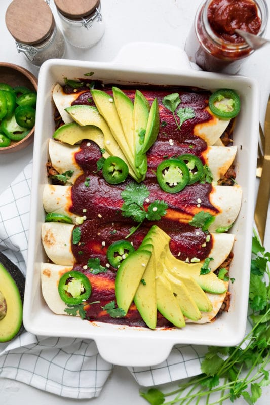5 Jackfruit enchiladas topped with avocado and jalapeno slices.