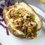 Baked potato topped with pulled jackfruit topped with BBQ sauce and chives.