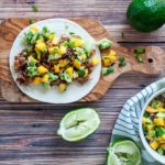 Pulled Jackfruit tacos topped with a mango salsa, limes on table.