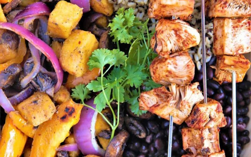 White plate containing grilled jackfruit on skewers, rice, black beans and grilled vegetables.
