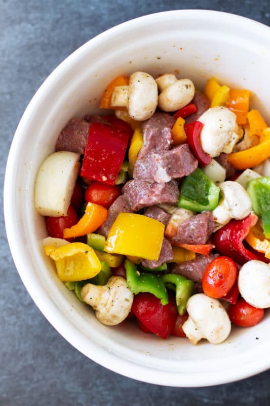 Bowl containing steak and vegetables marinated in Italian seasoning.