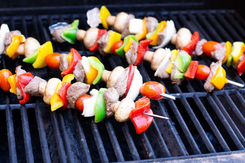 Four steak and vegetable skewers on the grill.