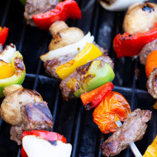 Steak and vegetables on three metal skewers on a grill.