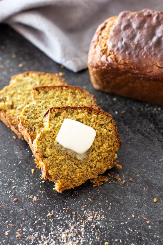 Sliced Quinoa Banana Bread with melted butter.