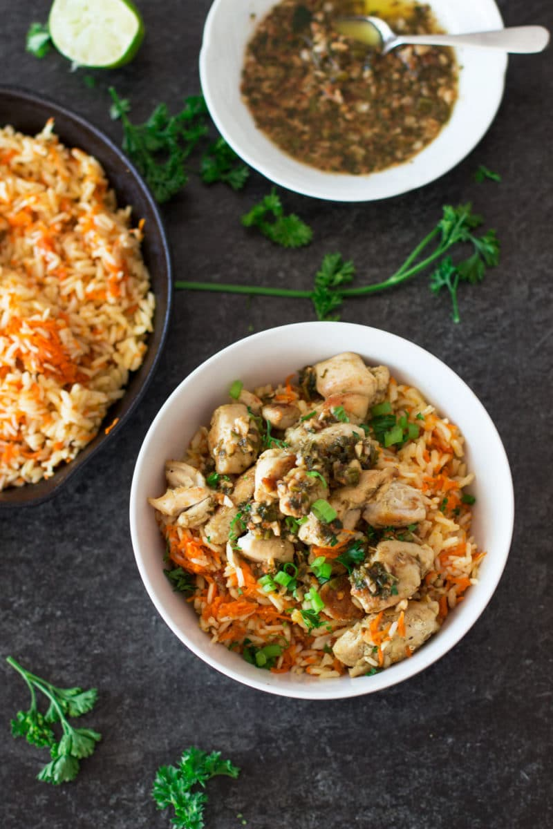 White bowl containing chicken over carrot rice topped with sauce, sauce and carrot rice on side of table.