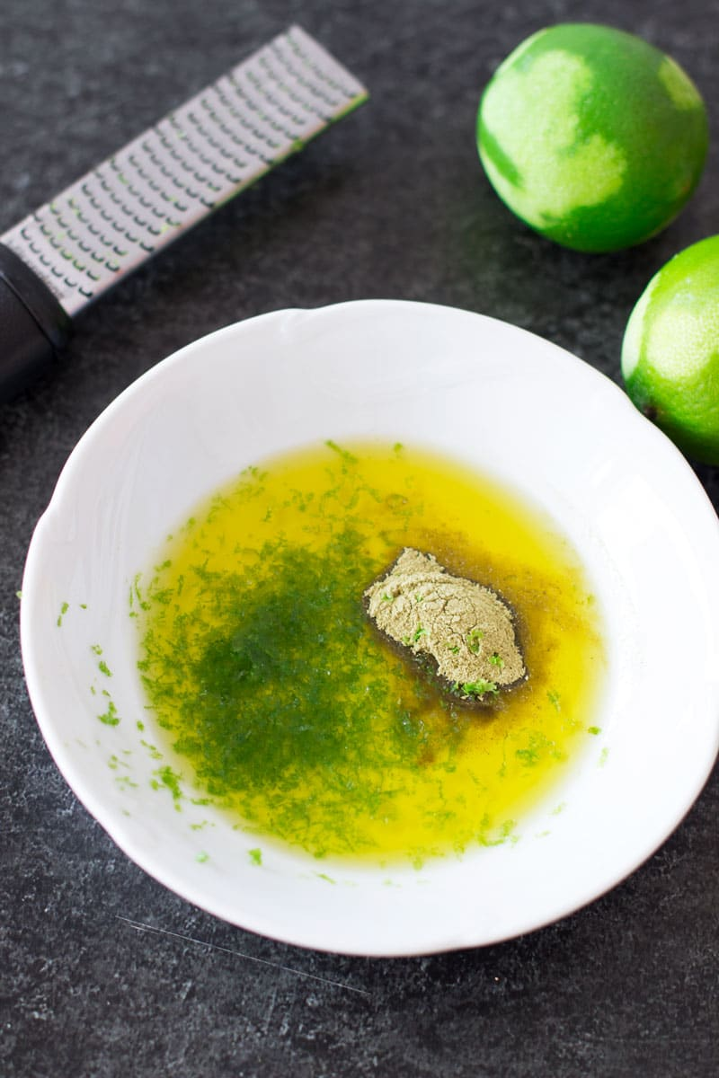 Olive oil, lime zest, and coriander in a dish, limes and zester on counter.