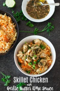 White bowl containing bowl of carrot rice topped with bite-sized chicken breasts and sauce, parsley on table.