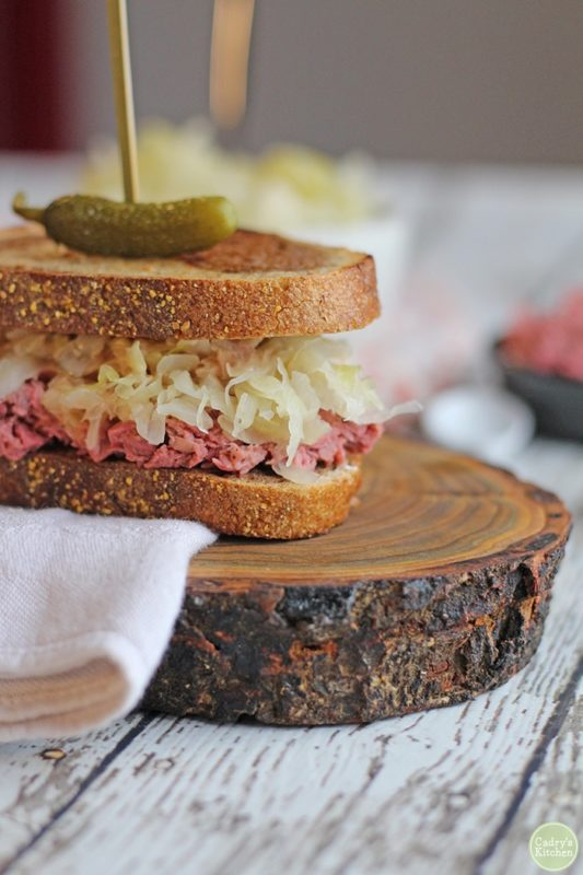 A Reuben sandwich topped with a sweet pickle.