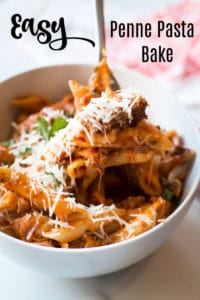 White bowl containing pasta, fork full of cooked penne pasta with melted mozzarella cheese.