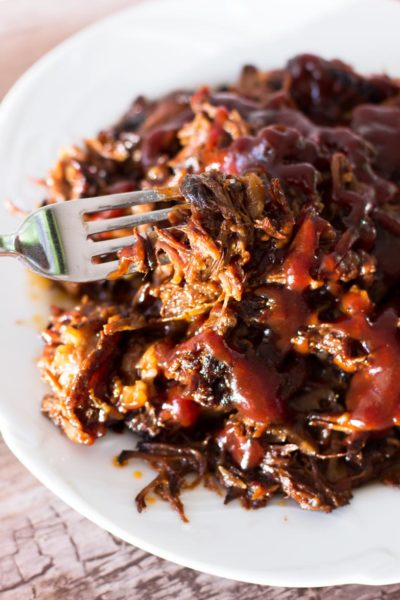 Fork containing shredded ribs topped with BBQ sauce on a white plate.