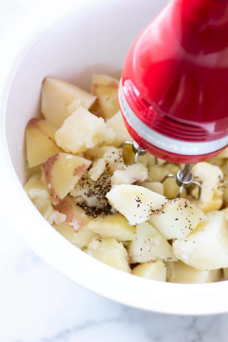 Red electric mixer mashing potatoes.