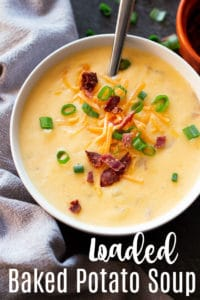 White bowl containing loaded potato cheese soup topped with green onions, bacon, and cheese.