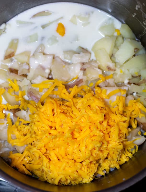 Pot with cooked potatoes, milk and shredded cheese.