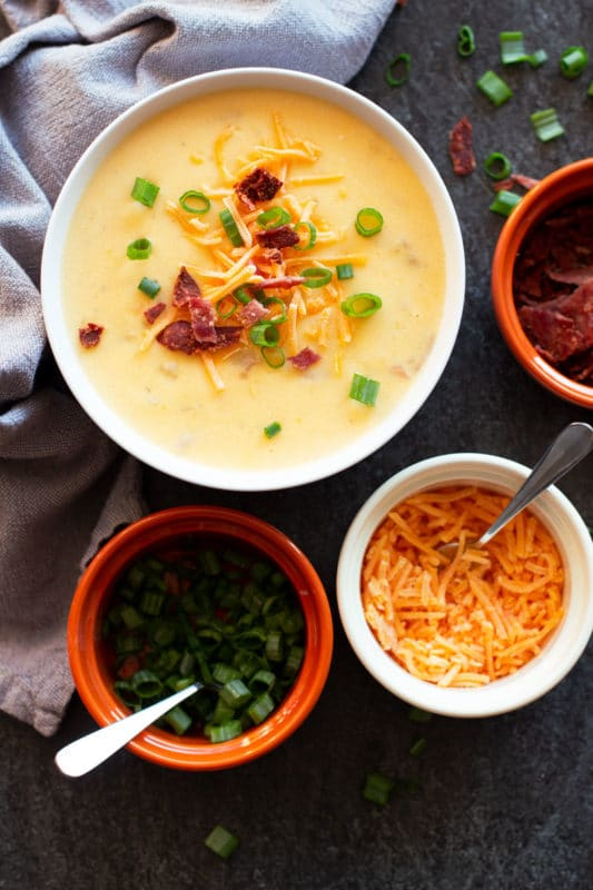 Bowl of Loaded Baked Potato Cheese Soup with bacon, green onion, and cheese on table.