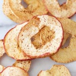 Dehydrated cinnamon apple rings on marble counter.