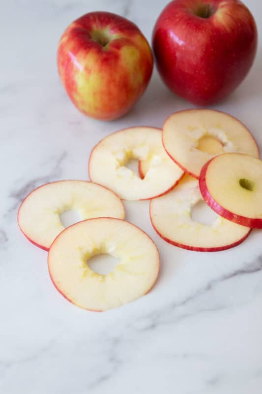 6 apple rings on a marble countertop.