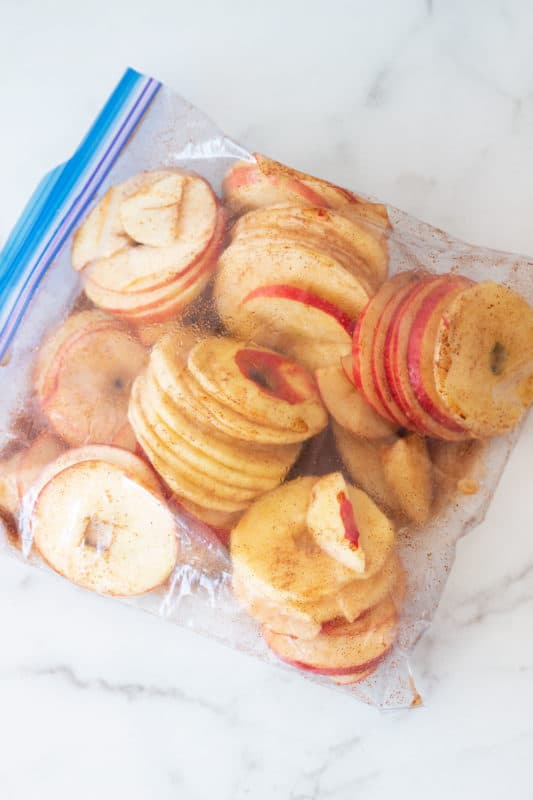 Gallon Ziplock bag containing sliced apple rings with a cinnamon marinade.