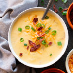 Bowl of Potato Cheese Soup, spoon in bowl topped with cheese, bacon, and onions.