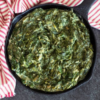 Cast iron skillet containing backed creamed spinach recipe on counter.