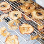 Dehydrated apple rings on 3 trays in a food dehydrator.