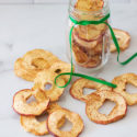 Jar filled with dehydrated cinnamon apples, apple rings on table.