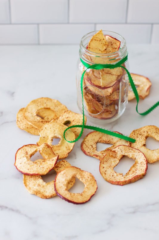 Dehydrated Apple Cinnamon apples on a marble counter and in a mason jar.