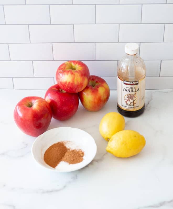Apples, lemons, vanilla extract, ground nutmeg, cinnamon, and sugar on counter.