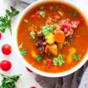 White bowl containing Vegetable Beef Soup topped with fresh cilantro, cherry tomatoes on table.