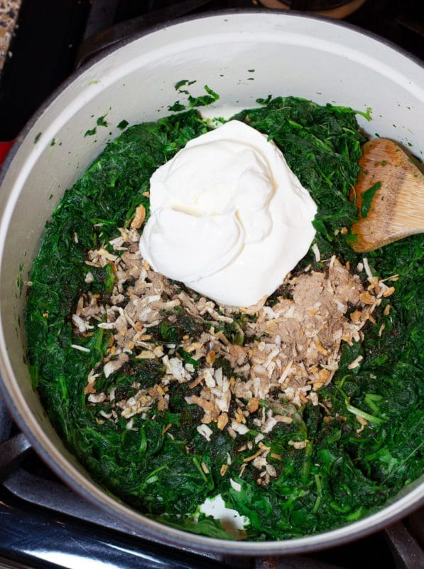 Pan containing cooked spinach leaves, sour cream, and dry onion soup mix.