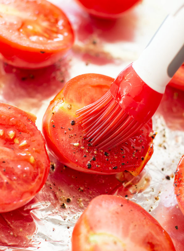 Basting olive oil onto tomato.