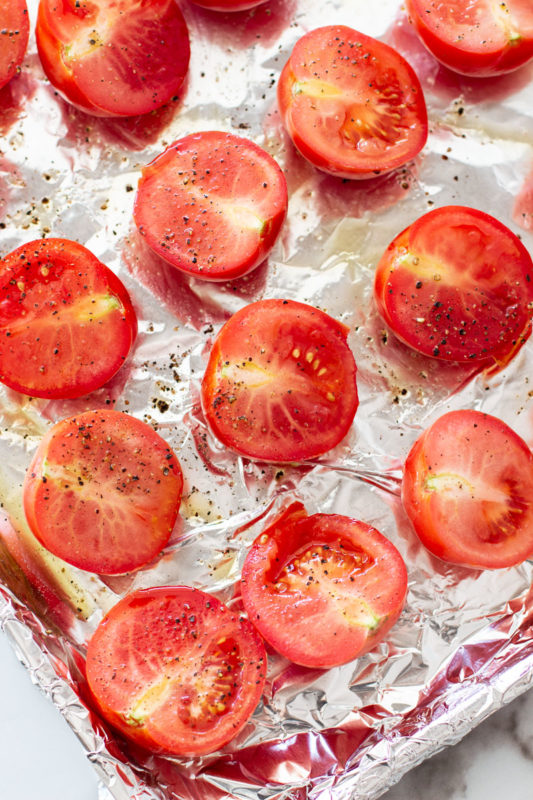 Cookie sheet lined with aluminum foil topped with fresh tomatoes cut lengthwise topped with salt and pepper.