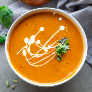 White bowl containing creamy tomato basil soup.