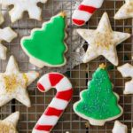11 sugar cookies consisting of Christmas tree, snowflake, and candy cane sugar cookies on a cooling rack.