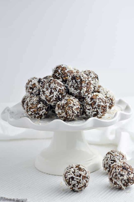 12 no bake snowflake balls topped with coconut on a white platter.