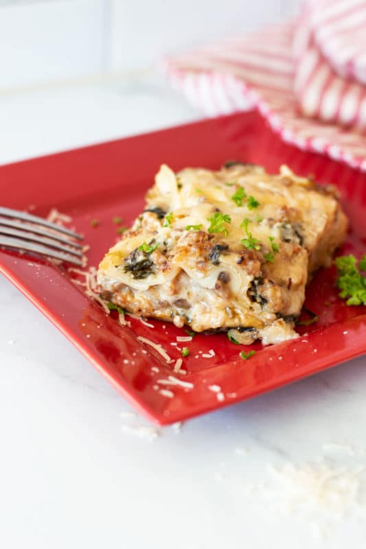 Slice of Creamy Spinach and Mushroom White Lasagna, fork on plate.