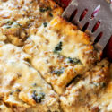 Slice of white sauce spinach lasagna on a spatula coming out of a pan.