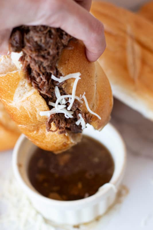 French Dip Sandwich being dipped in au jus.