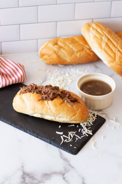 French Dip Sandwich on a counter, au jus dipping sauce and bread on counter.