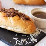 French Dip Sandwich on a counter, dipping sauce and bread on counter.