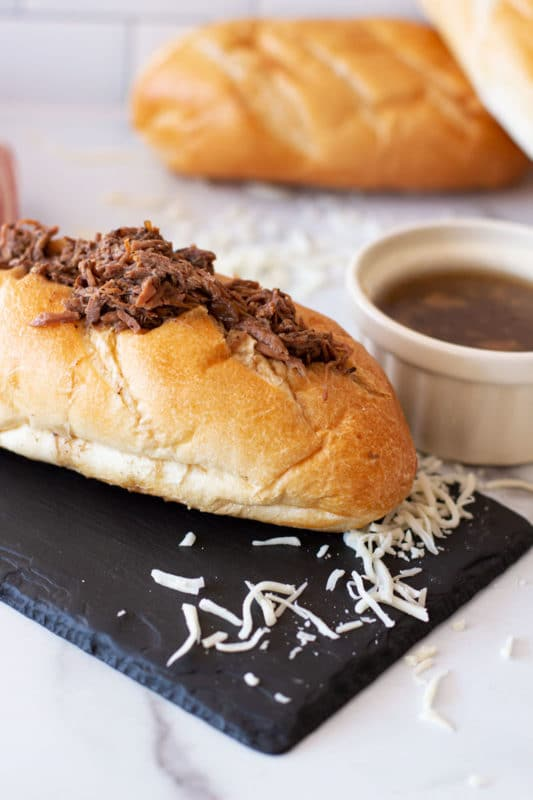 French roll containing shredded beef and cheese, au jus in bowl.