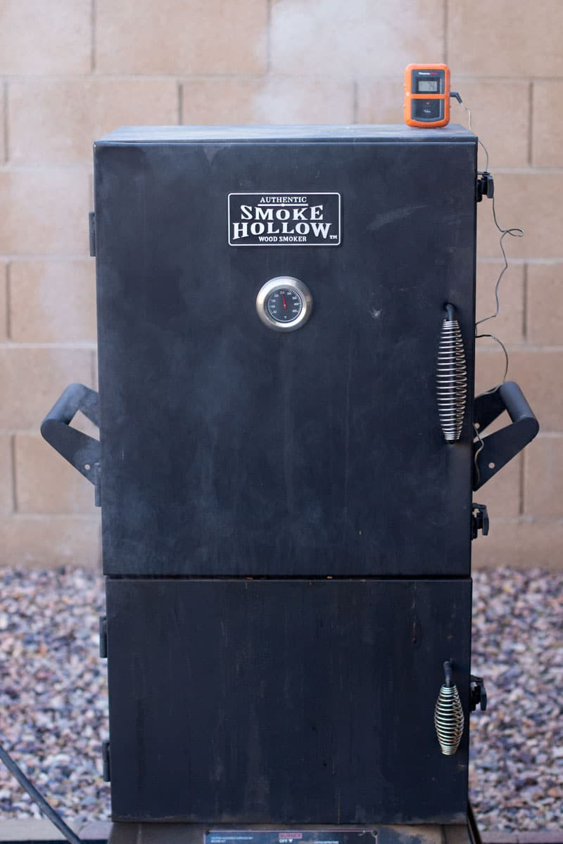 Smoke coming out of a smoker, temperature gauge on smoker.