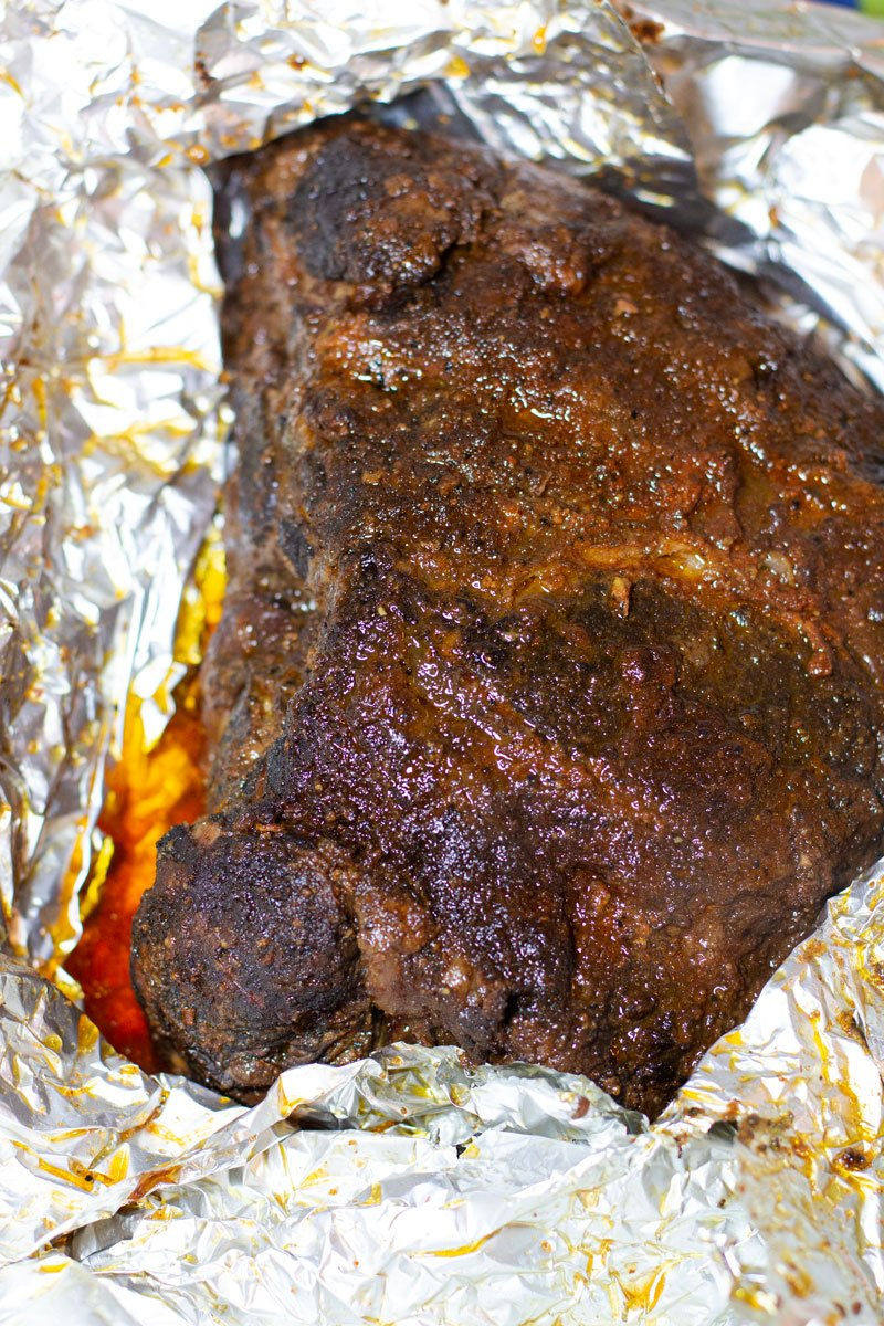 Smoked pork shoulder being unwrapped from an aluminum foil packet.