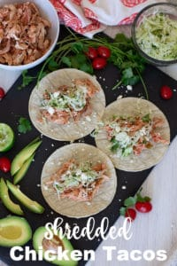 3 corn tortillas topped with shredded chicken and cilantro coleslaw.