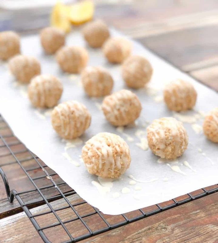 Cheesecake truffles on parchment paper over wire rack with lemon.