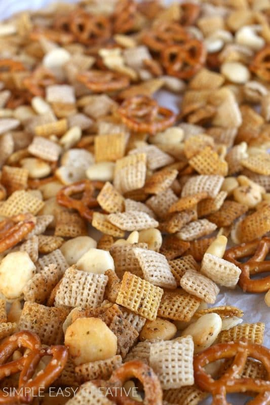 chex mix with pretzels and ranch seasoning on a baking sheet