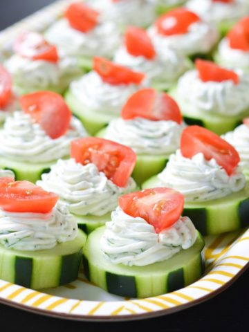 Sliced cucumbers with piped cheese and yogurt topped with tomatoes.