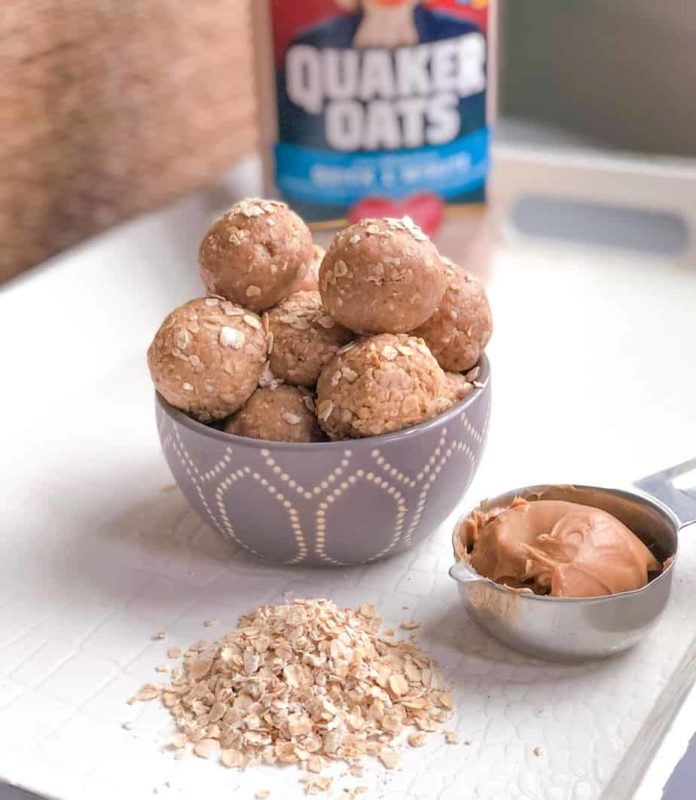 Peanut butter energy balls with oatmeal on table and a measuring cup filling with peanut butter.
