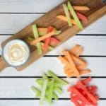 Sticks of melon in piles on cutting board with yogurt dip on the side.