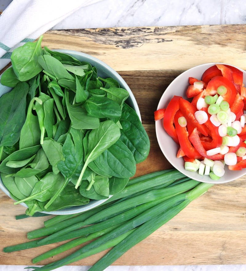 Fresh spinach, red peppers, and green onions in a bowl.